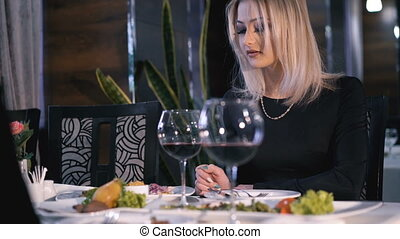 Stylish girls eating, drinking wine and speaking at fashionable restaurant