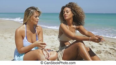 Stylish girls sitting on sandy beach - Beautiful multiethnic...