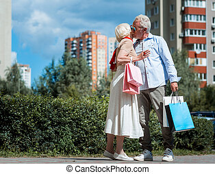 Stylish grey haired woman kissing her beloved husband