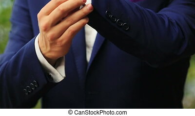 Stylish groom in blue luxury suit wearing cufflinks close up...