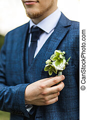 Stylish groom in classic blue suit holding flower boutonniere. Rustic wedding