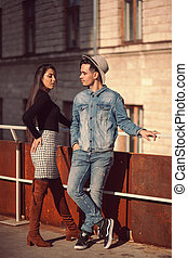 Stylish guy and girl posing in front of the camera on the street.
