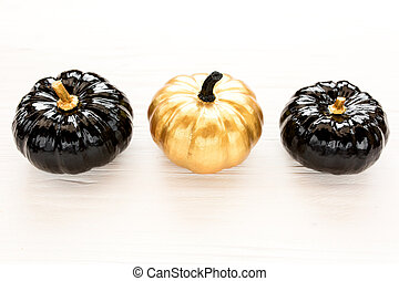 Stylish Halloween decorations. Decorative pumpkin black and gold Halloween isolated on white background. Flat lay, top view.