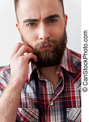 Stylish handsome. Close up of handsome young man in smart casual holding hand on beard