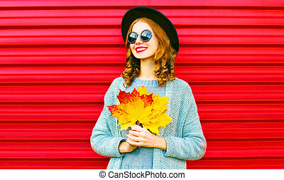 Stylish happy portrait smiling woman with yellow maple leaves on a red background