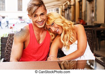 Stylish happy young couple behind table in a summer cafe
