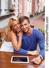 Stylish happy young couple with tablet pc behind table in a summer cafe