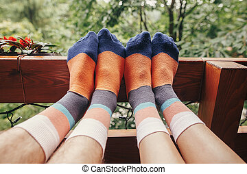 stylish hipster couple legs on wooden porch in colorful socks, in wooden cottage in forest in mountains. happy family relaxing together concept. summer vacation. funny moments
