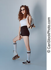 Stylish hipster girl in sunglasses posing with roller skates isolated on grey