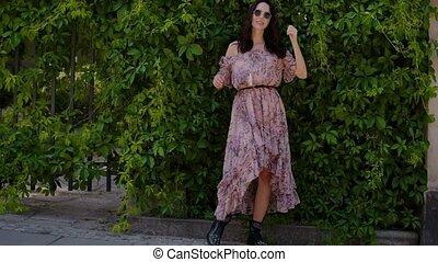 Stylish hipster girl posing over green leaves bush...