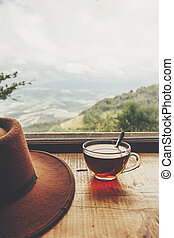 stylish hipster hat and glass of hot tea on wooden table at window light with view on mountains and sky. delicious drink on mountain top. summer travel and wanderlust. space for text
