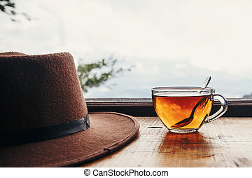 stylish hipster hat and tea in glass with spoon on wooden table at window light with view on mountains and sky. delicious hot drink on mountain top. summer travel and wanderlust. space