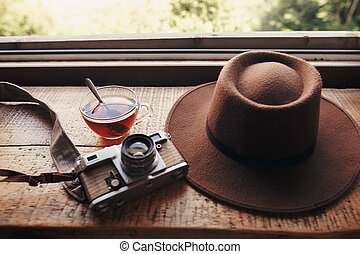 stylish hipster hat, photo camera and tea in glass with spoon on wooden table at window light with view of mountains and sky. summer relax concept. travel and wanderlust.