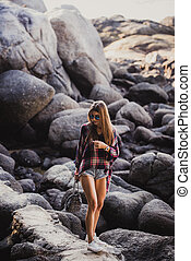 Stylish hipster woman in checkered shirt and shirts on summer beach at sunset. Path in a rocks at beach