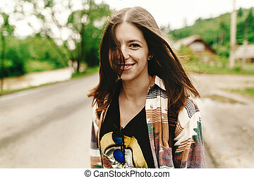 stylish hipster woman smiling and relaxing, calm mood in sunny  in summer mountains road, travel concept