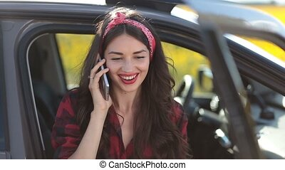 Stylish hipster woman talking on phone in the car
