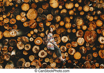 stylish hipster woman with backpack sitting at pile of firewood, save the environment and forest concept, atmospheric moment, human scale