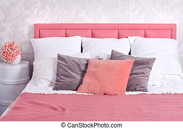 Stylish interior of modern bedroom. White and pink design of cozy bedroom with flowers. King-size bed with pink and grey bedding