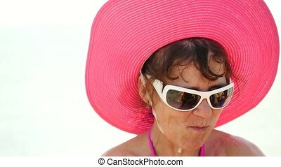 Stylish lady in a hat and sunglasses smiles at sea and eats...
