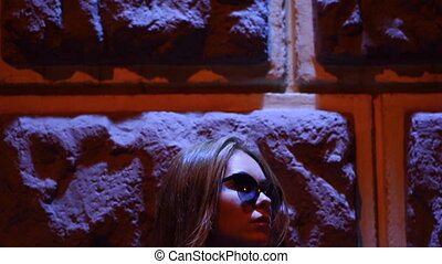 stylish lady with glasses stands near a wall in the background of the red light district late