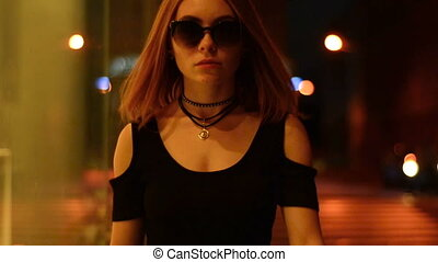 stylish lady with short hair in glasses goes around the city in the evening