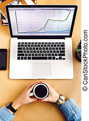 stylish laptop phone and succulent on craft background girl hands holding coffee,  working and marketing , flat lay