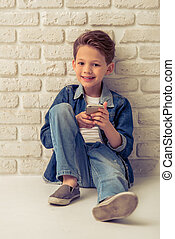 Stylish little boy in jeans clothes is using smartphone,...