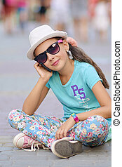 Stylish little girl child wearing a jeans clothes and sunglasses posing in the city
