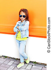 Stylish little girl child wearing a sunglasses and jeans clothes over orange background