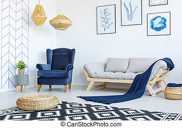 Stylish blue and white living room interior with armchair and sofa