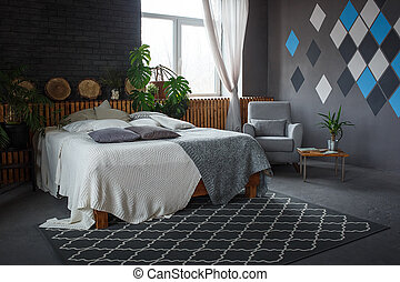 Stylish loft cozy living room with double bed, carpet, armchair, green plants and geometrical patterns on the wall
