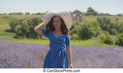 Stylish lovely woman walking in lavender blossoms - Elegant...
