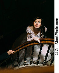 Stylish luxury bride in white dress looking up posing on old wooden stairs, top view