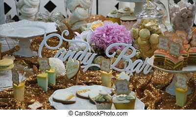 stylish luxury decorated candy bar with frosting cake at the golden birthday party, holiday celebration concept