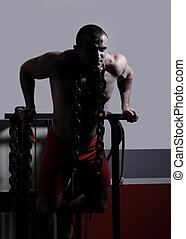 stylish male bodybuilder with a heavy chain standing in the gym.