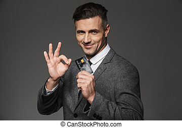 Stylish man 30s in businesslike suit and tie holding plastic credit card and gesturing alright sign, isolated over gray background
