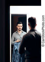 Stylish  Man Checking Himself in the Mirror Trying on Clothes