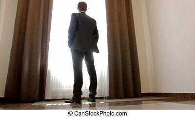 stylish man in black suit looking out the window