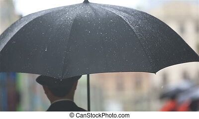 Stylish man in hat walks with umbrella on rainy street. Back view