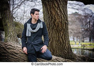 Stylish Man Leaning on Tree Trunk Looking Afar