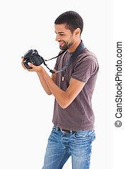 Stylish man looking at digital camera