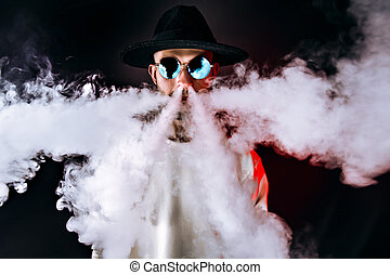 Stylish man puffing vapor - Stylish man in sunglasses...