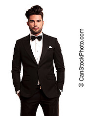 stylish man in elegant black suit and bowtie standing with hands in pockets on white background