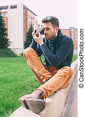 Stylish man using vintage camera