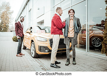Stylish mature father wearing red jacket presenting car to his son