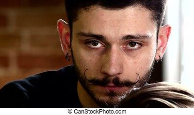 Stylish men's hairdresser: Barber mustache curls client. The...