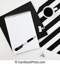 Stylish minimalistic workspace with book, notebook, pencil, cup of coffee, isolated on striped black and white background. Flat lay style Top view. Square crop.
