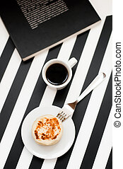 Stylish minimalistic workspace with smartphone mock up, book, cup of coffee, bakery, isolated on striped black and white background. Flat lay style Top view.