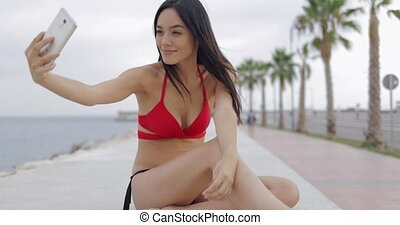 Stylish model taking selfie on tropical seafront