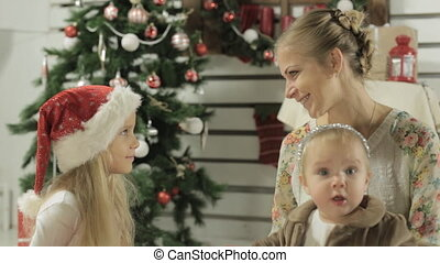 Stylish mother with two young daughters sitting next to beautiful Christmas tree